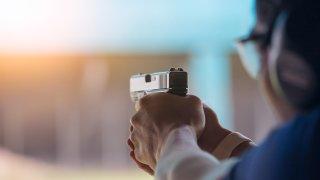 A person aiming a handgun at a gun range.