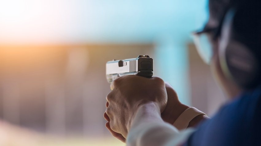 A person aiming a handgun at a gun range.