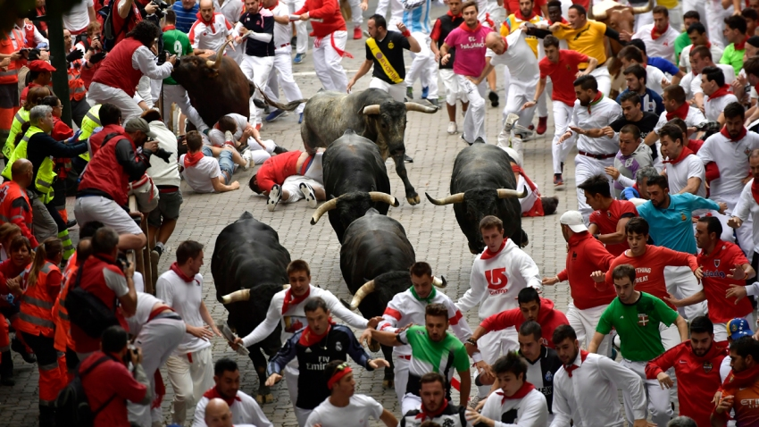 In this July 14, 2017, file photo, revellers fall next to Miura's fighting bulls during the running of the bulls at the San Fermin Festival, in Pamplona, northern Spain.