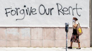 In this May 1, 2020, file photo, a woman wearing a mask walks past a wall bearing graffiti asking for rent forgiveness amid the COVID-19 pandemic in Los Angeles, California.