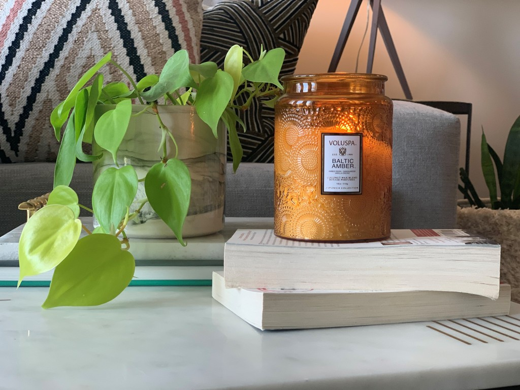 A candle sits atop books on a desk.
