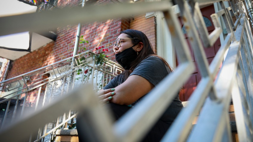 """Natalia Afonso, 27, an international student from Brazil at Brooklyn College, sits on a stoop outside her home during an interview, Thursday, July 9, 2020, in New York. Afonso, who is studying teaching education and finished her first semester this spring, said she has lived in the U.S. for 7 years and """"I don't see myself moving back to Brazil at this point."""