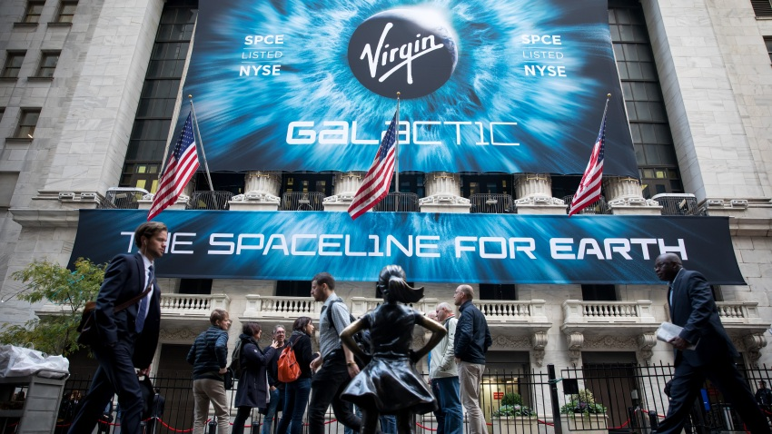 Pedestrians pass in front of a banner displaying Virgin Galactic Holdings Inc. signage during the company's initial public offering (IPO) outside the New York Stock Exchange (NYSE) in New York, U.S., on Monday, Oct. 28, 2019.
