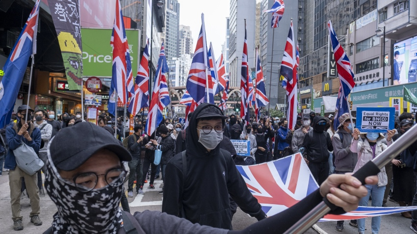 Demonstrators wave the British Union flag, also known as a Union Jack, as they march during a protest on Hennessy Road in the Causeway Bay district of Hong Kong, China, on Wednesday, Jan. 1, 2020.