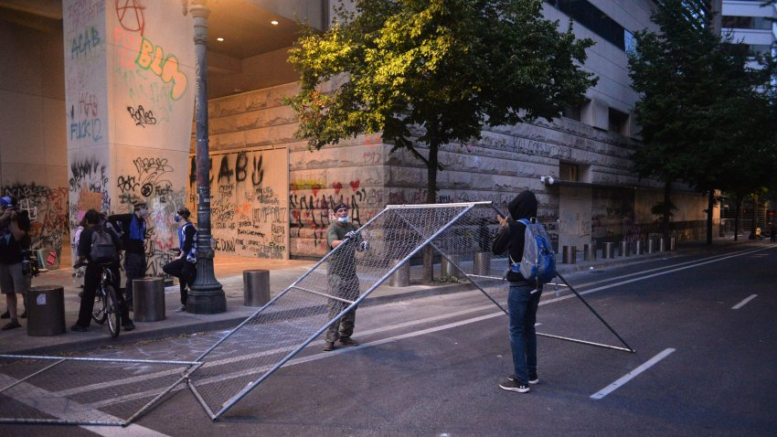 Protestors remove a fence and move it to another area to block a road near the Multnomah County Justice Center in Portland, Oregon