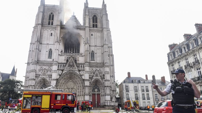 """A French Police officer gestures as firefighters are at work to put out a fire at the Saint-Pierre-et-Saint-Paul cathedral in Nantes, western France, on July 18, 2020. - The major fire that broke out on July 18, 2020 inside the cathedral in the western French city of Nantes has now been contained, emergency services said. """"It is a major fire,"""" the emergency operations centre said, adding that crews were alerted just before 08:00 am (0600 GMT) and that 60 firefighters had been dispatched."""