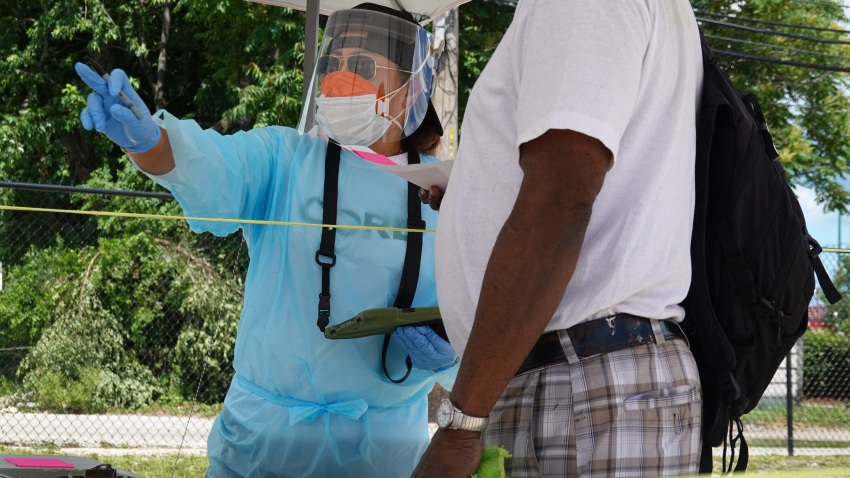 Workers check in residents at a mobile COVID-19 testing site set up on a vacant lot