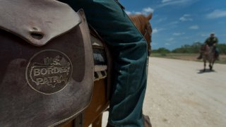 The U.S. Border Patrol logo is seen on a satchel while agents work on horseback near Carrizzo Springs, Texas, U.S., on Thursday, July 3, 2014. The Border Patrol finds an average of one corpse a day in the badlands near the U.S.-Mexico border; in the past 15 years, the toll has reached 5,570, exceeding all U.S. combat deaths for the Iraq war.