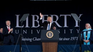 President of Liberty University Jerry Falwell (L) and others clap as US President Donald Trump prepares to speak during Liberty University's commencement ceremony May 13, 2017 in Lynchburg, Virginia.