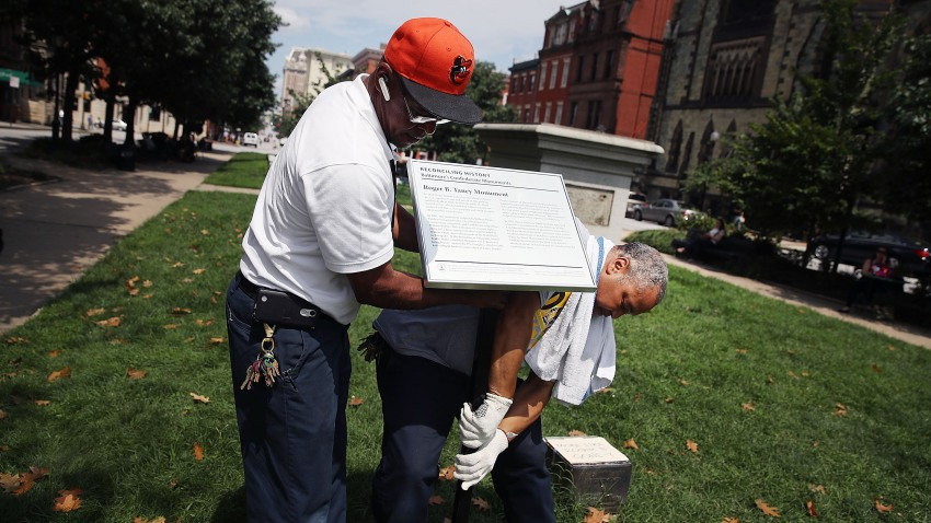 City workers remove a plaque near the pedestal that was formerly the base for a statue of Roger B. Taney, former Chief Justice of the U.S. Supreme Court and majority author of the Dred Scott decision, August 16, 2017 in Baltimore, Maryland.