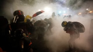 Federal officers launch tear gas at a group of demonstrators during a Black Lives Matter protest at the Mark O. Hatfield United States Courthouse Sunday, July 26, 2020, in Portland, Ore.