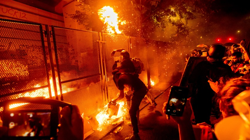 Protesters throw flaming debris over a fence at the Mark O. Hatfield United States Courthouse on Wednesday, July 22, 2020, in Portland, Ore.