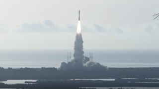 A rocket carrying a Mars rover lifts off.