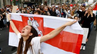 A woman reacts as she marches holding an old Belarusian national flag in the center of Minsk, Belarus, Friday, Aug. 14, 2020. Some thousands of people have flooded the cnetre of the Belarus capital, Minsk, in a show of anger over a brutal police crackdown this week on peaceful protesters that followed a disputed election.