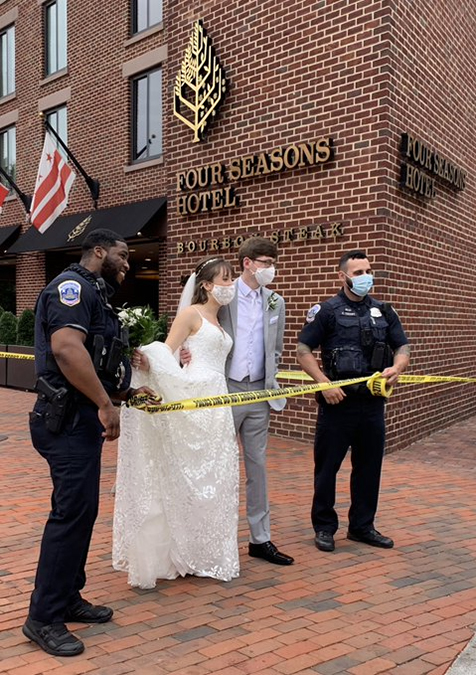 A bride and groom and two police officers stand behind yellow tape at the Four Seasons Hotel after its evacuation.