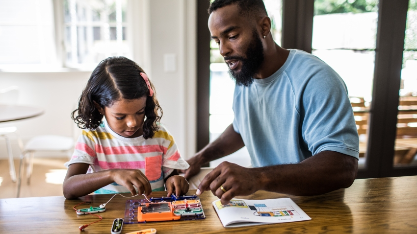 A photo of a father and daughter working on a science project at home.