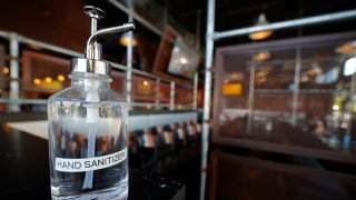 A bottle of hand sanitizer is seen at the hostess stand of Bad Daddy's Burger Bar as it reopened for dine-in seating