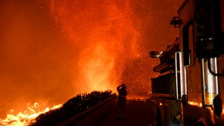 A firefighter observes a fire tornado from an overpass above the 101 freeway on December 6, 2017 in Ventura, California