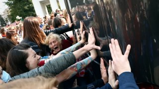 Women block a police bus during an opposition rally to protest the official presidential election results in Minsk, Belarus