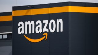 In this file photo, the logo of Amazon is seen on the facade of the company logistics center.