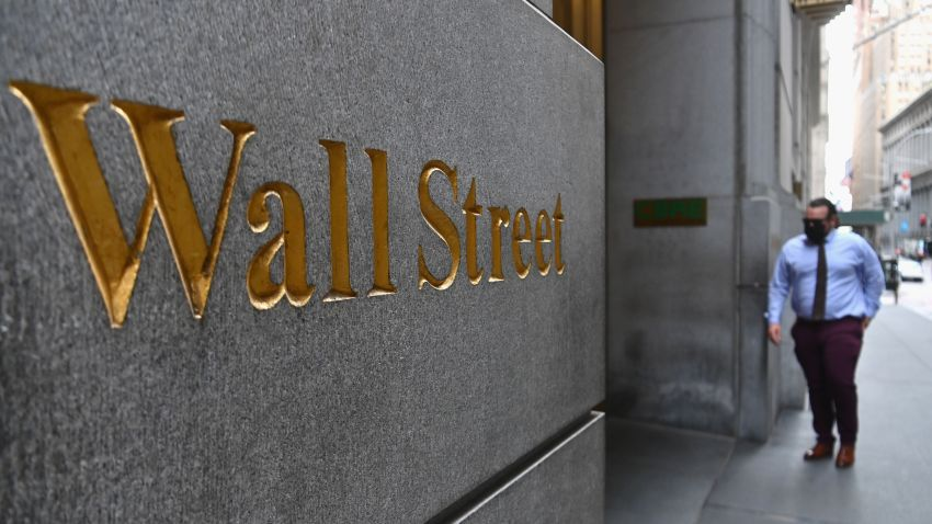 A man walks near the New York Stock Exchange (NYSE) on August 31, 2020 at Wall Street in New York City. - Wall Street stocks paused near record levels early Monday ahead of key economic data later in the week, with a newly-tweaked Dow index edging lower. The final session of a heady August opened on a lackluster note as markets await employment data and updates on the manufacturing and services sectors in the coming days. About 15 minutes into trading, the Dow Jones Industrial Average was down 0.4 percent to 28,539.83.