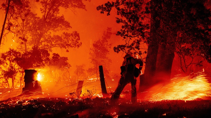 In this Sept. 7, 2020, file photo, a firefighter works the line as flames push towards homes during the Creek fire in the Cascadel Woods area of unincorporated Madera County, California.