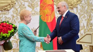 Lidiya Yermoshina (L), Chairperson of the Belarusian Central Election Commission, hands over a presidential ID to Belarus' President-Elect Alexander Lukashenko during his inauguration ceremony at the Palace of Independence on September 23, 2020.