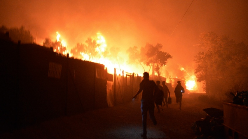 Refugees and migrants run as fire burns in the Moria refugee camp on the northeastern Aegean island of Lesbos, Greece, on Wednesday, Sept. 9, 2020. Fire Service officials say a large refugee camp on the Greek island of Lesbos has been partially evacuated despite a COVID-19 lockdown after fires broke out at multiple points around the site early Wednesday.