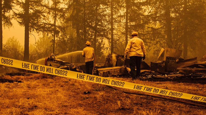Oregon firefighters work behind caution tape in Mill City, Oregon, Sept. 10, 2020, as they battle the Santiam Fire.