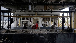 People walk through burnt toll gates with anti police slogans sprayed across, in Lagos