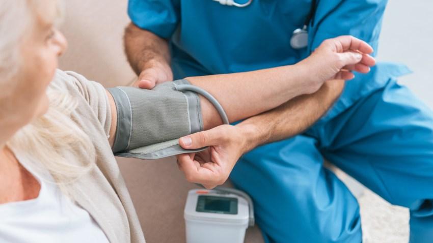 cropped shot of caregiver measuring blood pressure to senior woman
