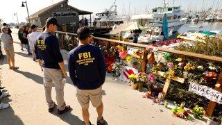 Members of the FBI dive team view a growing memorial.