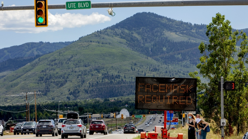 "Pedestrians walk in front of a street sign that reads ""Face Mask Requried"" in Summit County near Park City, Utah"