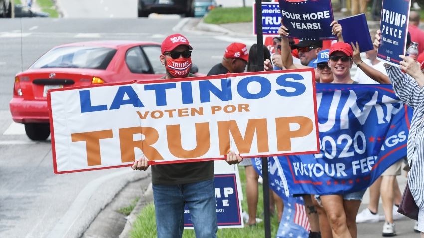 Supporters hold placards after Vice President Mike Pence addressed supporters at a Latinos for Trump campaign rally at Central Christian University on Oct. 10, 2020 in Orlando, Florida. With 24 days until the 2020 presidential election, both Donald Trump and Democrat Joe Biden are courting the Latino vote as Latinos are the largest racial or ethnic minority in the electorate, with 32 million eligible voters.