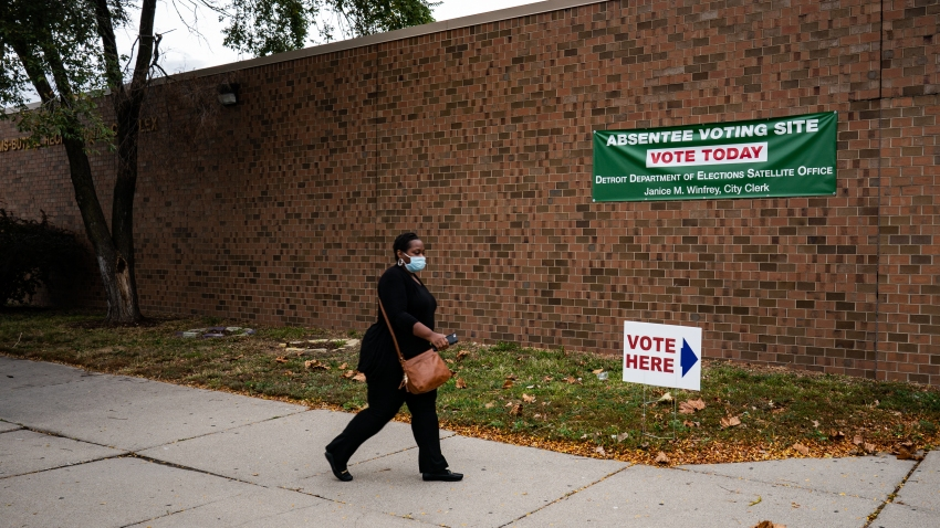 A person walks to cast absentee ballot