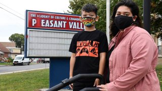 Kristina Negron poses for a photograph with her son, Mason Negron, 6, at his Pleasant Valley Elementary school, Sept. 29, 2020, in Schenectady, N.Y. Negron was laid off from her job as an aide for a special education class at Schenectady High School due to budget cuts.