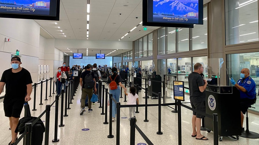A Transportation Security Administration (TSA) agent wearing a protective face mask and sitting behind a barrier checks the identification of a traveler at the airport security screening center in Salt Lake City, Utah, Oct. 8, 2020.