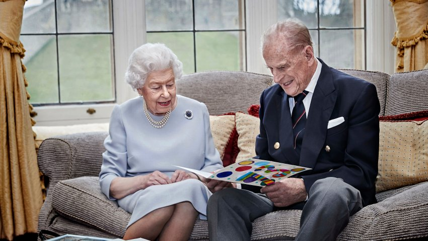 Britain's Queen Elizabeth II and Prince Philip, Duke of Edinburgh look at a homemade wedding anniversary card, given to them by their great grandchildren Prince George, Princess Charlotte and Prince Louis, as the royal couple sit in the Oak Room at Windsor Castle