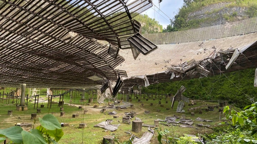 In this Aug. 11, 2020, file photo, provided by the Arecibo Observatory, shows the damage done by a broken cable that supported a metal platform, creating a 100-foot (30-meter) gash to the radio telescope's reflector dish in Arecibo, Puerto Rico.