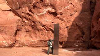This Nov. 18, 2020, photo provided by the Utah Department of Public Safety shows a Utah state worker inspecting a metal monolith that was found installed in the ground in a remote area of red rock desert in Utah. The smooth, tall structure was found during a helicopter survey of bighorn sheep in southeastern Utah, officials said Monday.