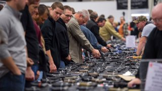 People look at handguns as thousands of customers and hundreds of dealers sell, show and buy guns and other items during The Nation's Gun Show at the Dulles Expo Center Oct. 3, 2015.
