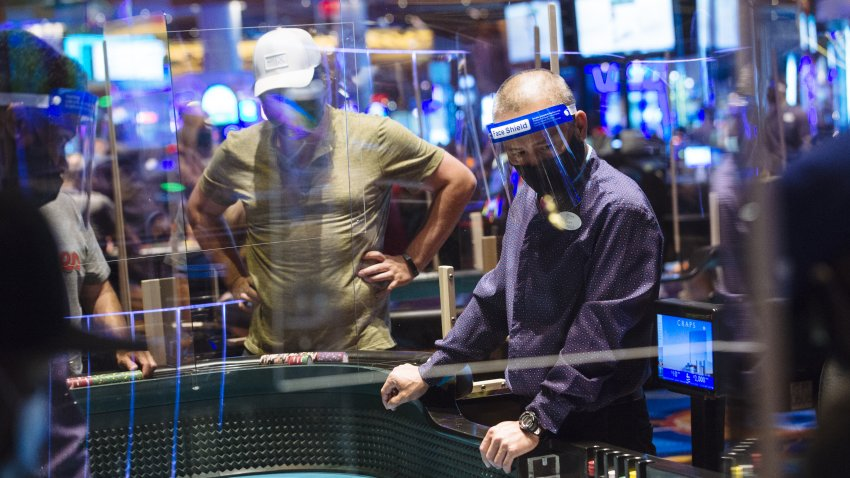 An employee wears a protective mask and face shield while overseeing the craps table at the Ocean Casino Resort during the Covid-19 pandemic in Atlantic City, New Jersey, U.S., on Thursday, July 2, 2020.