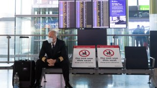 A member of flight crew sits next to social distancing signs in the check-in area in at London Heathrow Airport Ltd. in London, U.K., on Saturday, Dec. 19, 2020.