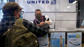 United Airlines gate attendant Daniel Chester assists a passenger before a flight to Honolulu at SFO
