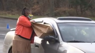 Woman pushes bag into car through window for a coat drive