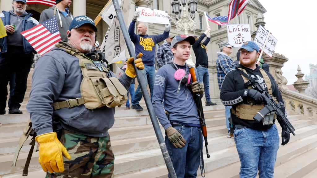 """People take part in a protest for """"Michiganders Against Excessive Quarantine"""" at the Michigan State Capitol in Lansing, Michigan on April 15, 2020."""