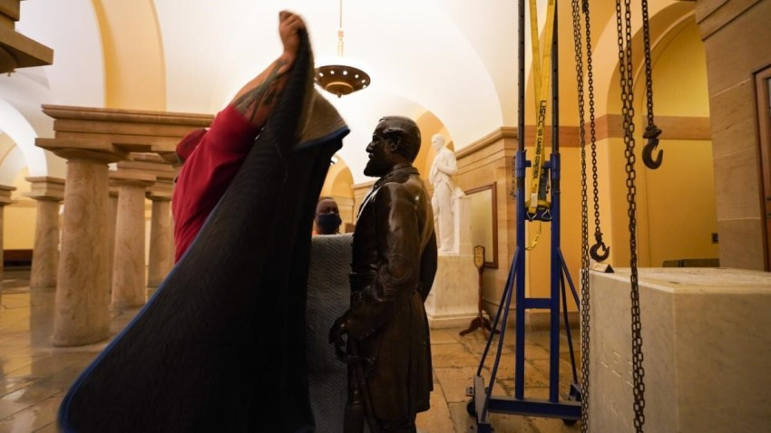 A worker is shown moments before covering a statue of Robert E. Lee with a cloth before it is removed from the U.S. Capitol. The statue had already been removed from its pedestal, which is shown empty surrounded by a pulley system.