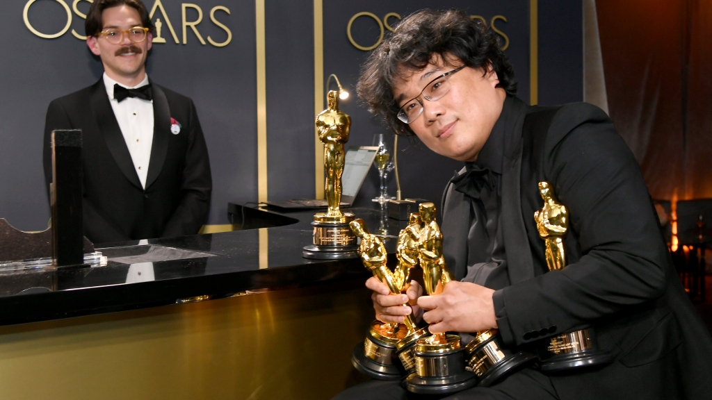 """Writer-director Bong Joon-ho, winner of the Best Picture, Director, Original Screenplay, and International Feature Film awards for """"Parasite,""""  holds the trophies won by his black comedy flick at the 92nd Academy Awards Governors Ball at Hollywood and Highland on Feb. 9, 2020, in Hollywood, California."""