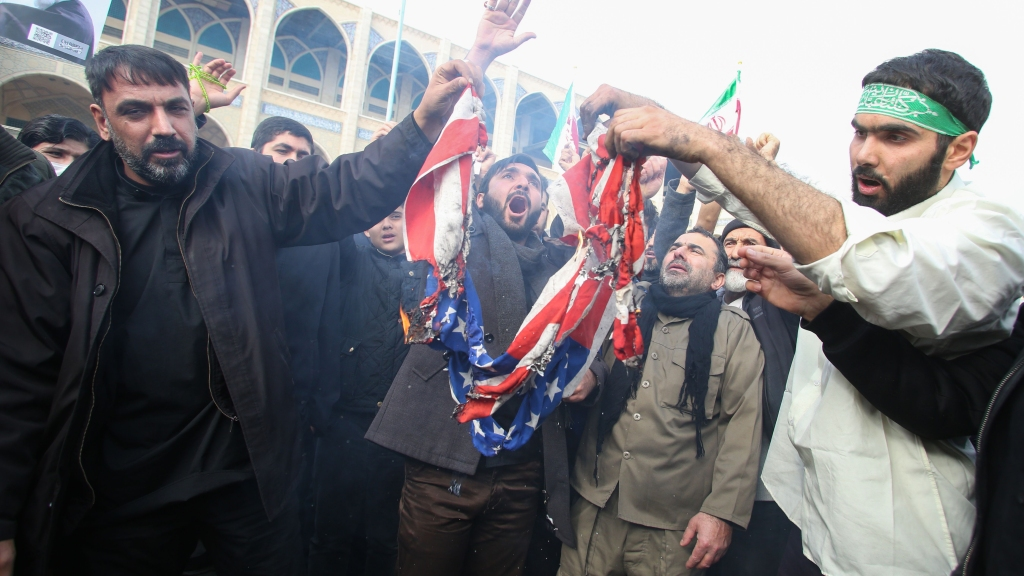 """Iranians burn a U.S. flag during a demonstration against American """"crimes"""" in Tehran on Jan. 3, 2020, following the killing of Iranian Revolutionary Guards Major General Qassem Soleimani in a strike on his convoy at Baghdad International Airport."""