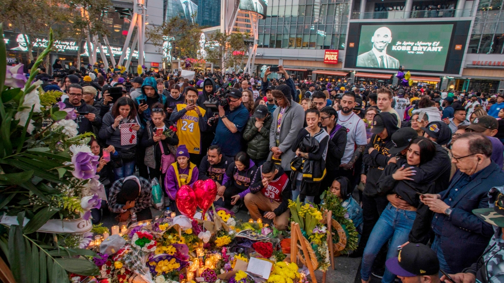 Mourners gather around a makeshift memorial for Kobe Bryant in front of the Staples Center in Los Angeles, Jan. 26, 2020.